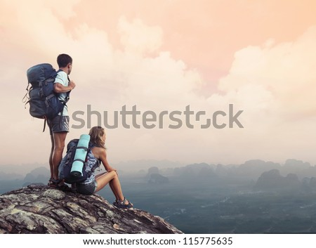 Two hikers with backpacks standing on top of a mountain and enjoying a valley view - stock photo