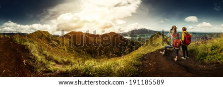 Two hikers with backpacks standing on top of the mountain enjoying valley view and taking a picture - stock photo