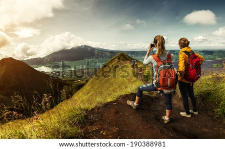 Two hikers with backpacks standing on top of the mountain enjoying valley view and taking a pictures - stock photo