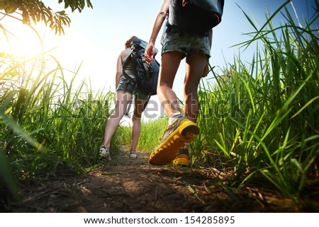 Two hikers with backpacks walking through lush green meadow - stock photo