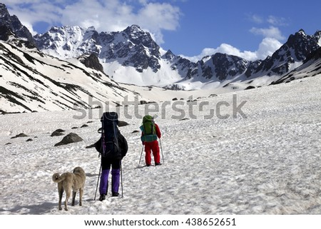 Two hikers with dog in spring snowy mountains. Turkey, Kachkar Mountains (highest part of Pontic Mountains). - stock photo