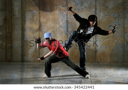 Two hip-hop dancers performing with a grungy background - stock photo