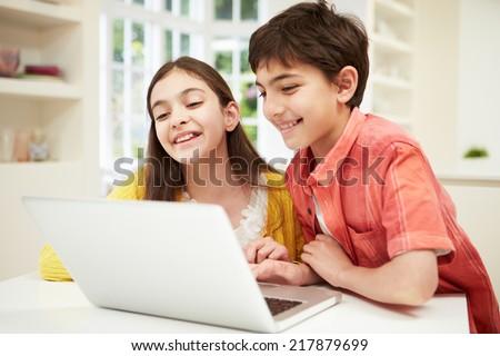 Two Hispanic Children Looking at Laptop - stock photo