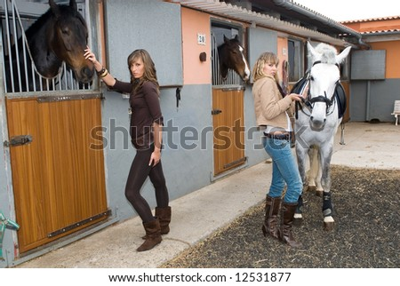 two hispanic girls with horses in the stable - stock photo