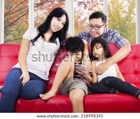 Two hispanic parents with their children on sofa using digital tablet with autumn background on the window - stock photo
