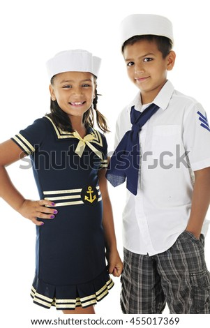 Two Hispanic siblings happily looking at the viewer as they stand together in their sailor outfits.  On a white background. - stock photo