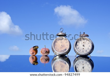two historical clocks and rotten apples on mirror and sky - stock photo