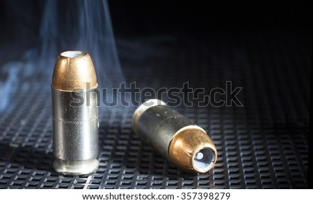 Two hollow point handgun cartridges with smoke - stock photo