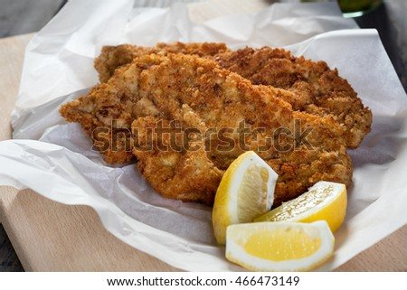 two homemade breadcrumbed viennese schnitzel with lemon slices