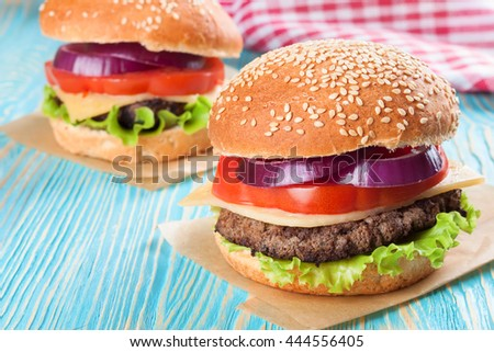 Two homemade cheeseburgers with beef patties and fresh salad on seasame buns, sered on blue wooden table. - stock photo