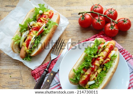 Two homemade hot dogs with fresh vegetables - stock photo