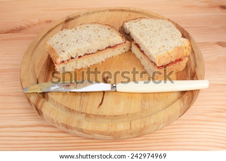 Two homemade PB&J sandwiches on a wooden board with a sticky knife - stock photo