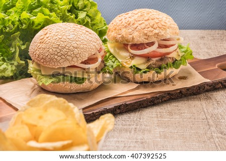 Two homemade vegetarian burgers with fresh organic vegetables on rustic wooden background - stock photo