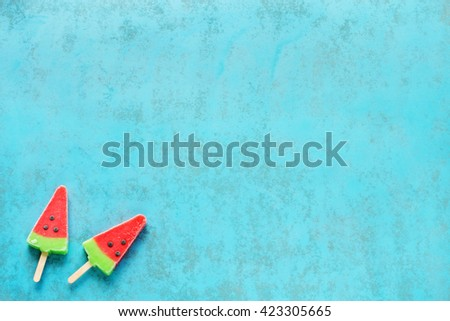 Two homemade watermelon popsicles on blue background. Copy space. - stock photo