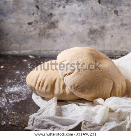 Two homemade wholegrain pita bread on white textile, served with flour over dark table. Square image with selective focus