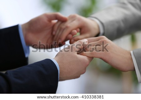 Two homosexuals holding each other hands on blurred background