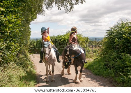 Two horse riders being nosy - stock photo