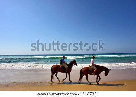 Two horse riders on beach. Shot in Sodwana Bay Nature Reserve, KwaZulu-Natal province, Southern Mozambique area, South Africa. - stock photo