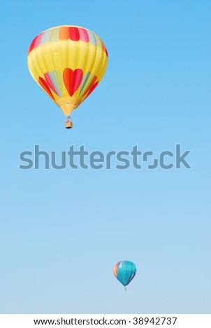Two hot air balloons against a blue sky - vertical - stock photo