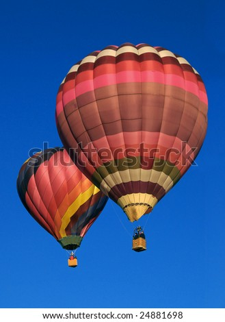 Two hot air balloons against blue sky