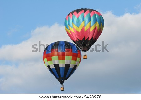 two hot air balloons flying side by side with a cloudy blue sky