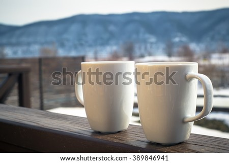 two hot chocolate cups outdoors - stock photo