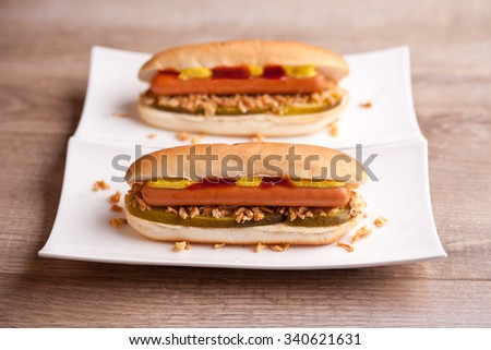 Two hot dogs with gherkin, onions, ketchup and mustard - stock photo