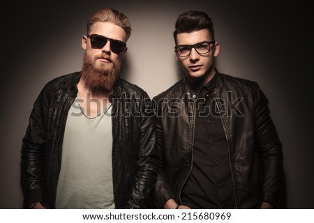 Two hot guys in leather jacket with glasses, looking at the camera, against studio background - stock photo