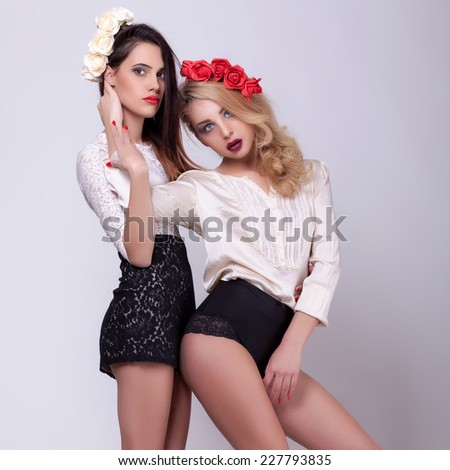 Two hot tall models full lenght on grey background. Professional make up and hairstyle. Studio lighting - stock photo