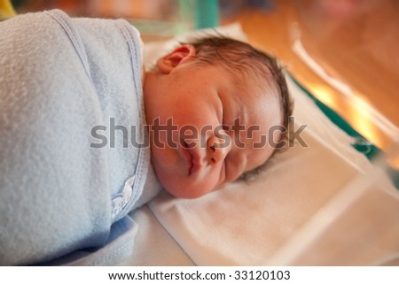 Two hours old baby resting in swaddling-clothes - stock photo