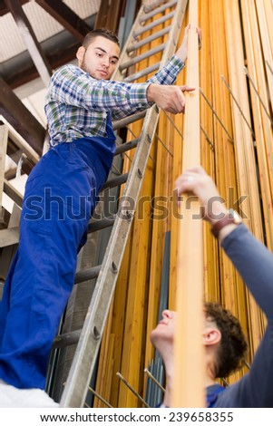 Two house-builder choosing PVC window profile at stand - stock photo