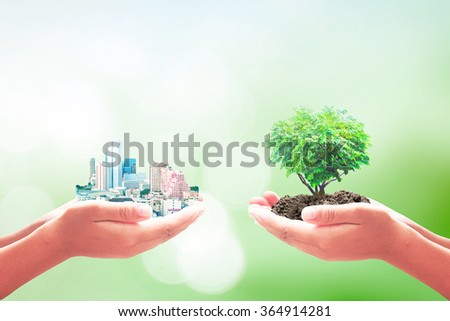 Two human hand holding the city and green heart of tree. Ecological City, World Environment Day, Sustainable Development, Love, Trust, Alternative Energy, Learning, Prosper, Education concept. - stock photo