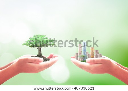Two human hands holding big tree and city of coins over blurred beautiful nature background. Investment CSR International Creativity and Innovation Day concept. - stock photo