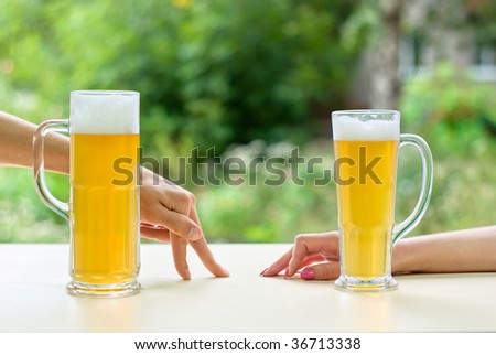 two human hands, man and woman with beer in glass.  Resting man and woman. - stock photo