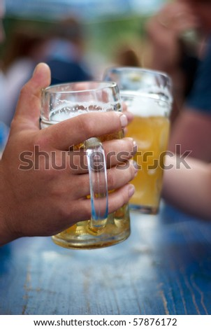 two human hands toast with a glasses of beer - stock photo