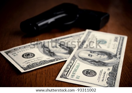 Two hundred-Dollars bills and gun on the wooden table - stock photo