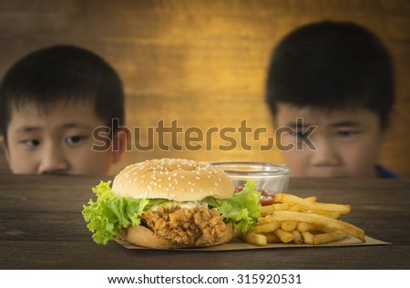 Two hungry children stared want to eat a burger on a wooden table. - stock photo