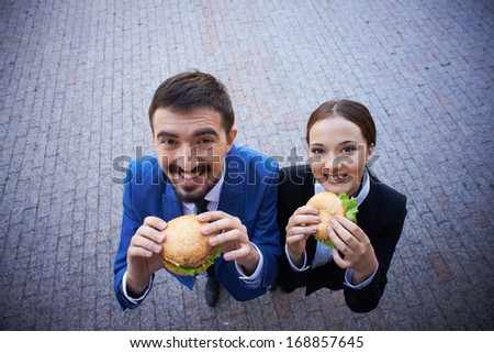 Two hungry colleagues eating sandwiches outside - stock photo