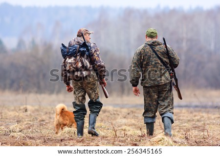 two hunters and dog on the field - stock photo