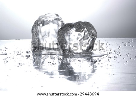 Two ice cubes in a mirror - stock photo
