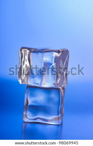 Two ice cubes on the blue background