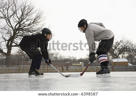 Two ice hockey player boys in uniform facing off on ice. - stock photo