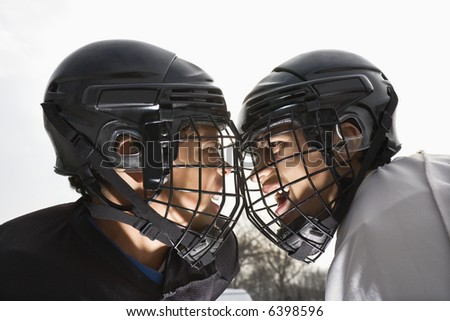 Two ice hockey players in uniform facing off trying to intimidate eachother. - stock photo