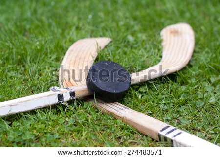 two ice hockey sticks with vintage old hockey puck on green grass background, Ice Hockey World Championships, used implements, natural and real photo - stock photo