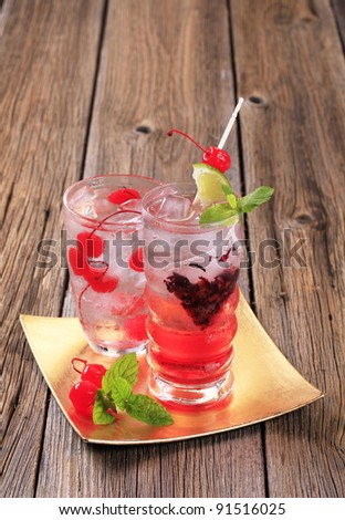 Two iced beverages with cherries, mint and lemon - stock photo