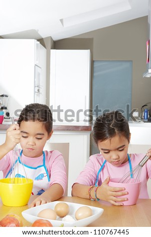 Two identical twin sisters beating eggs in their home kitchen while on vacations. - stock photo