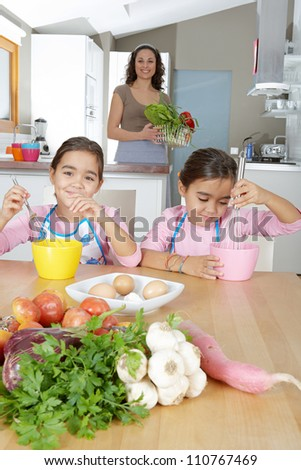 Two identical twin sisters beating eggs in their home kitchen while on vacations, while their mother stands behind them. - stock photo