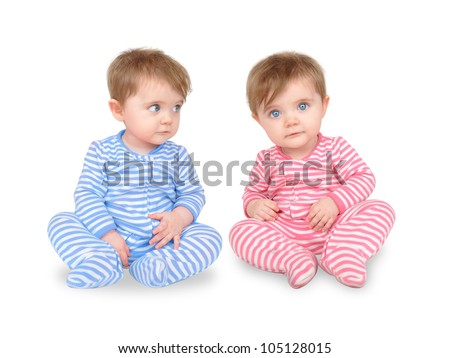 Two identical twins are sitting on a white isolated background. One boy is wearing blue and the other girl is wearing pink. Use it for a personality or family concept. - stock photo