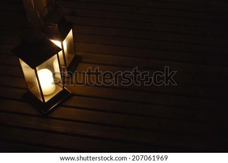 Two illuminated lanterns on deck at night - stock photo