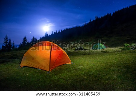 Two Illuminated orange and green camping tents under moon, stars at night  - stock photo